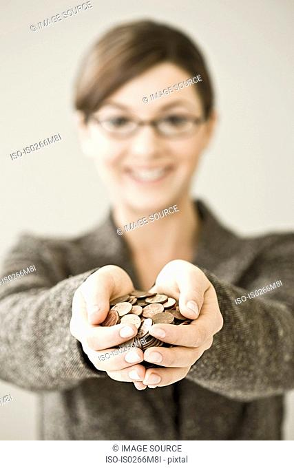 Young woman holding a pile of coins