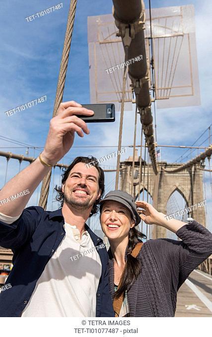 Happy couple taking selfie on Brooklyn Bridge