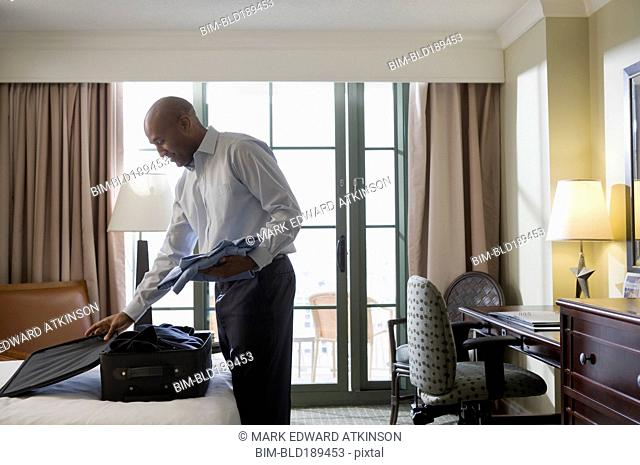 African businessman in hotel packing suitcase