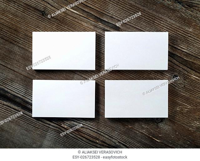 Blank cardboard business cards on a dark wooden table. Template for ID. Top view
