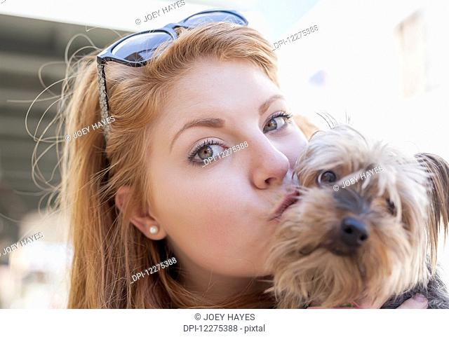 Red haired young woman holding and kissing her small dog; United States of America
