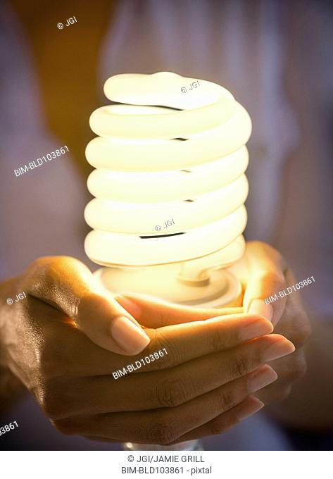Cape Verdean woman holding CFL light bulb