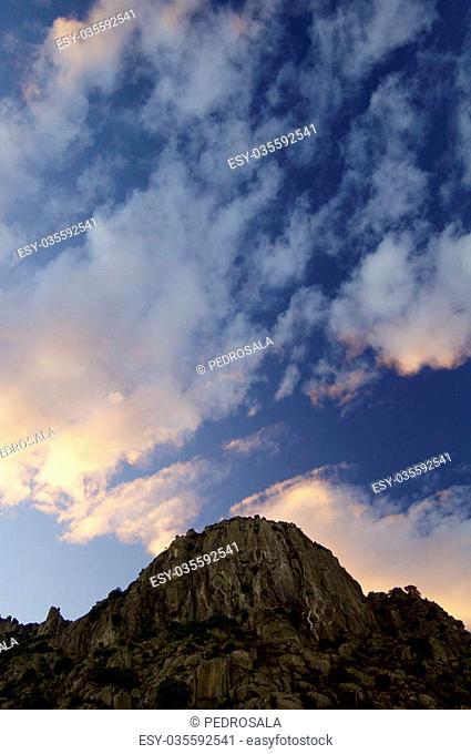Orange clouds and hill at sunset in Pico de La Miel, La Cabrera, Madrid, Spain