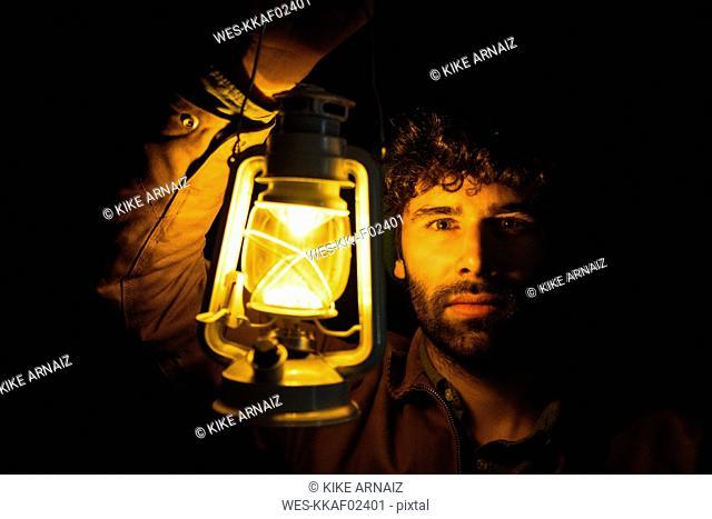 Portrait of man holding storm lantern in the dark