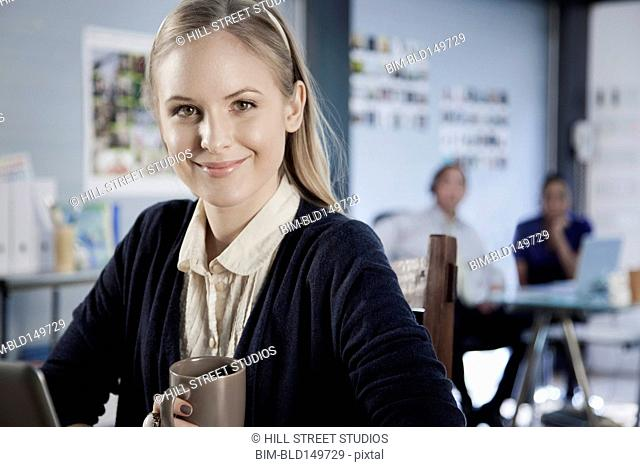 Caucasian businesswoman drinking coffee