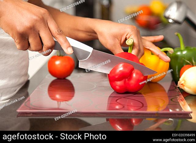 African American womans hand slicing a red pepper
