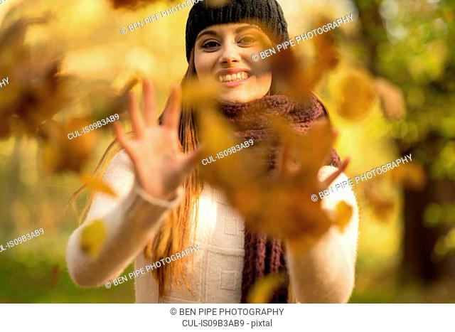 Young woman throwing autumn leaves in air, smiling