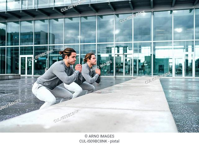 Young adult male twins training, squatting by wall in city
