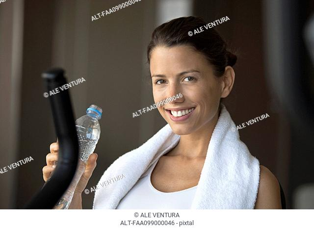 Woman hydrating with bottled water in health club
