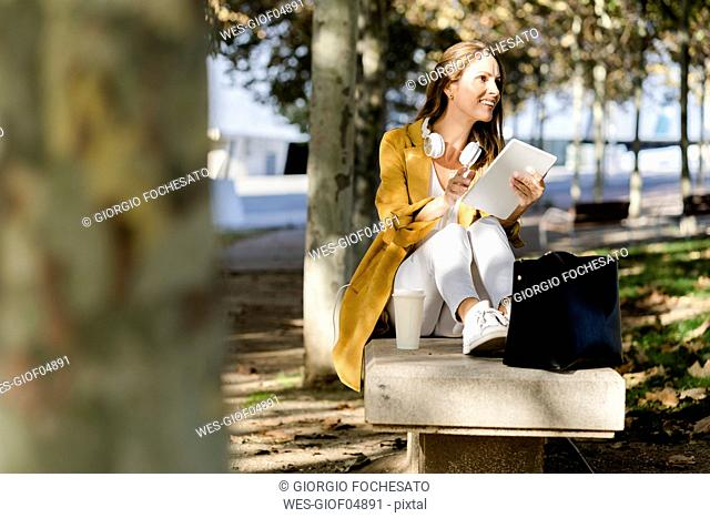 Smiling woman sitting on a bench in a park holding tablet