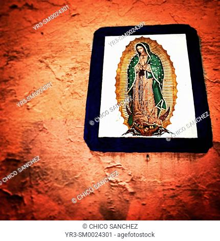 An image of Our Lady of Guadalupe decorates an orange wall in Coyoacan, Mexico City, Mexico