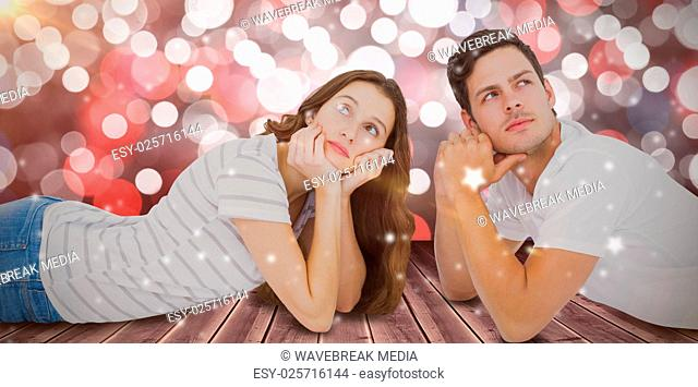 Composite image of couple lying on floor and looking up