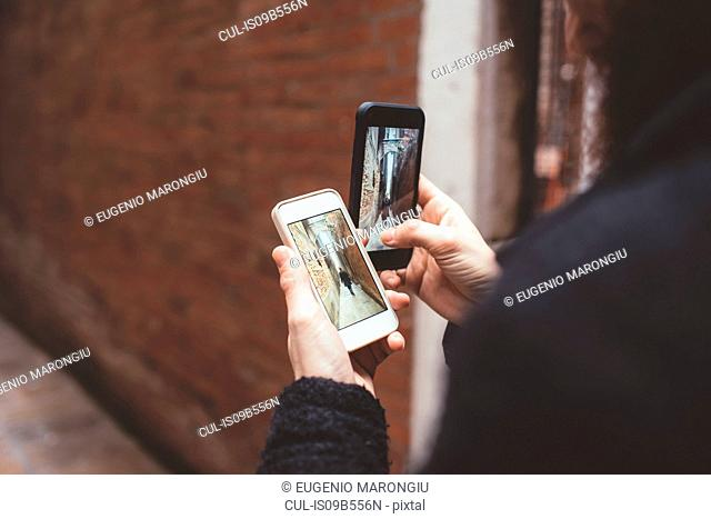 Over the shoulder view of man holding two smartphones with photographs of alley, Venice, Italy