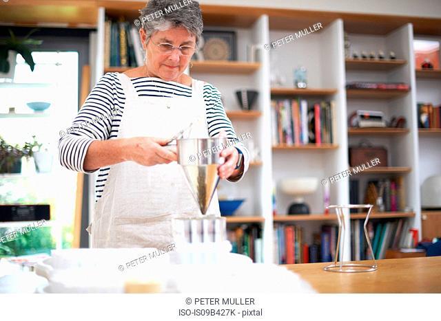 Senior woman using pancake funnel to pour mixture into plastic pots