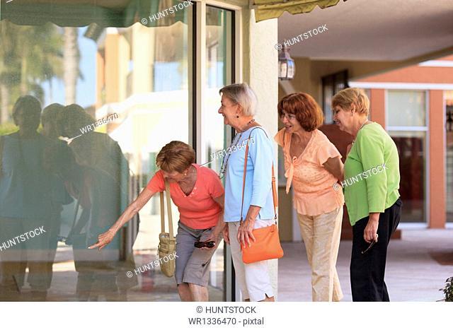 Senior friends looking in a store window