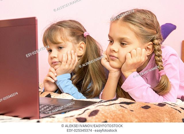 Two girls lying on his stomach on the bed looking at the laptop screen