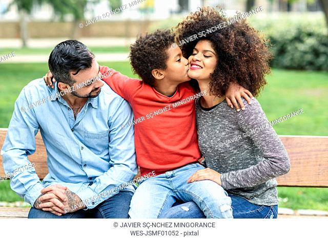 Family sitting on a park bench, son kissing mother