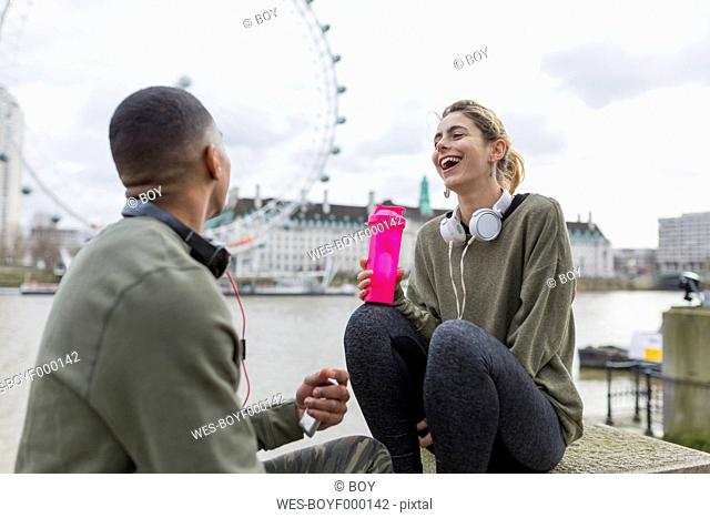 UK, London, two runners relaxing at riverwalk