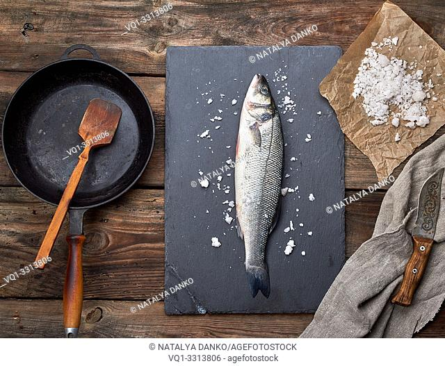 fresh whole sea bass fish on a black graphite board, next to it is an empty round black frying pan on a wooden table, top view