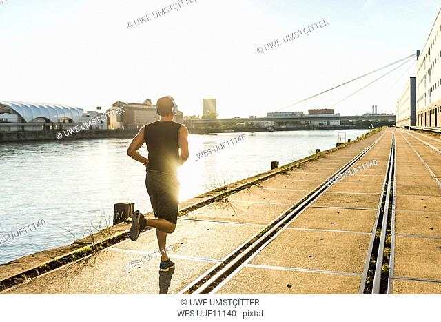 Young athlete jogging in the city at the river