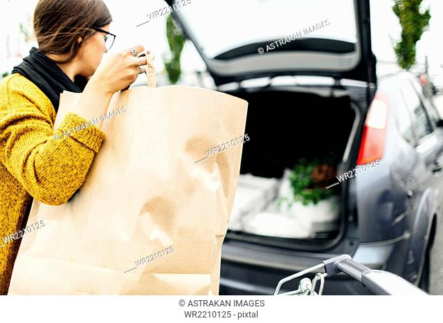 Young woman loading shopping bag into trunk of car