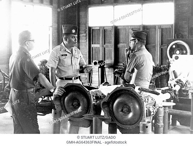 African-american lieutenant standing with two other American servicemen during the Vietnam War, in a heavy vehicle machine shop, one man smoking a cigarette