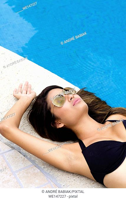 Young woman with aviator sunglasses relaxing poolside with eyes closed