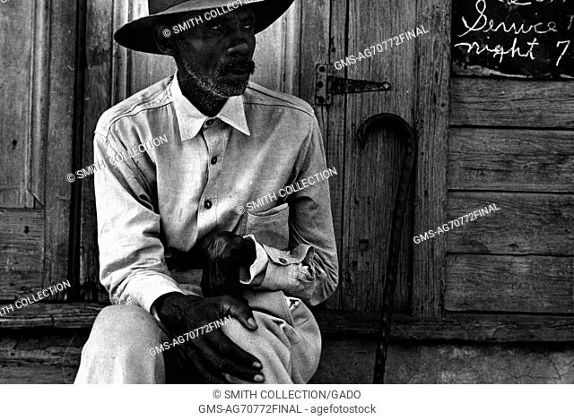 A man wearing a button down shirt and a hat is sitting on the steps of a church, a sign advertising the times for church services hangs on the side of the...