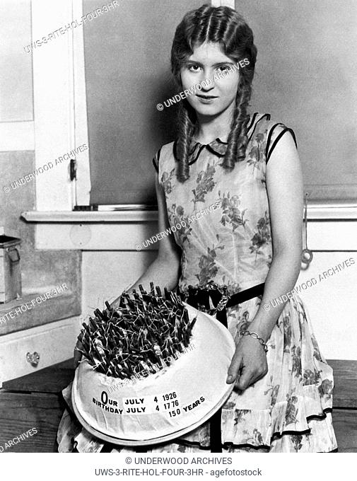 Los Angeles, California: July 4, 1926. A young woman with the special birthday cake she made in honor of the 150th birthday of the United States