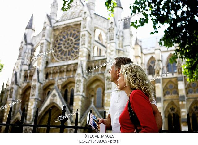 A middle-aged couple looking at Westminster Abbey, London