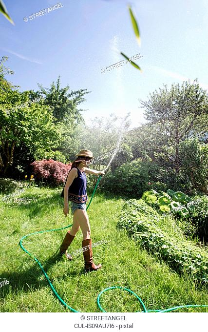 Side view of mature woman in garden squirting water into air with hosepipe