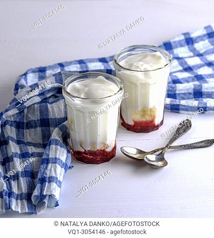 two glass glasses with homemade yogurt and raspberry syrup, next two iron spoons