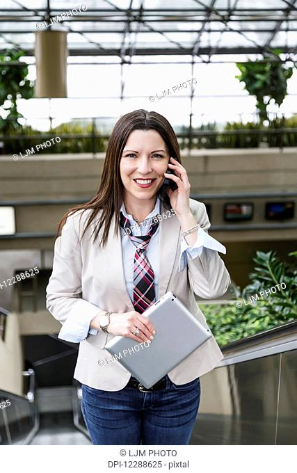 Business woman on an escalator talking on her cell phone and holding a tablet; Edmonton, Alberta, Canada
