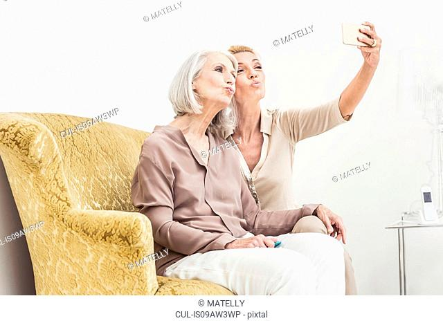 Adult mother and daughter, taking self portrait using smartphone