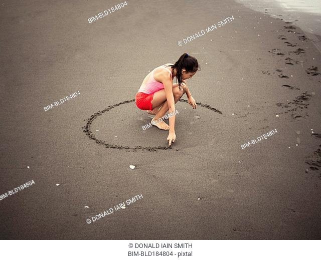 Mixed race girl drawing in beach sand