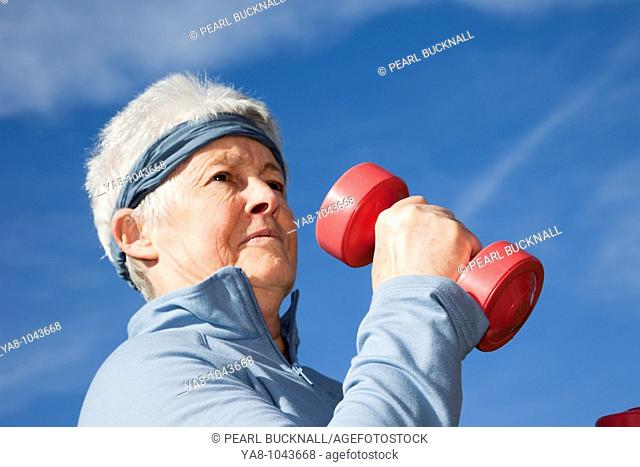Britain, UK, Europe  Senior woman exercising with dumbbell hand weights outdoors  MR 10/02