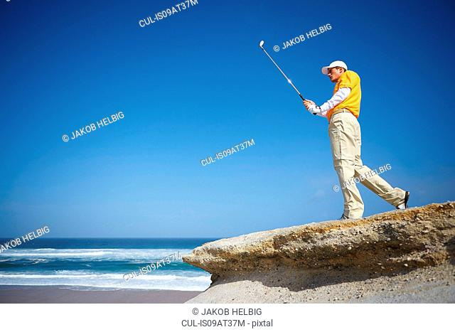Low angle view of golfer standing on cliff overlooking ocean holding golf club