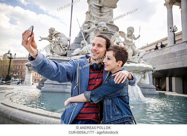 Young adult couple taking picture of themselves, Vienna, Austria