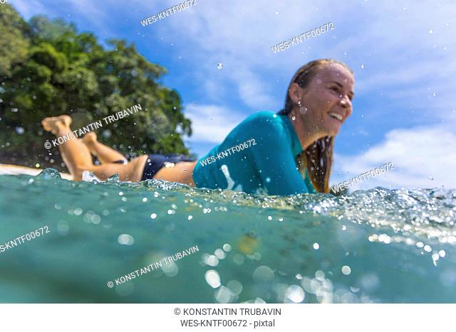 Indonesia, Java, smiling woman lying on surfboard on the sea