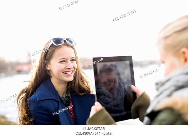 Teenage girl photographing friend with digital tablet