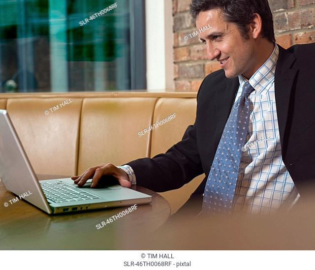 Businessman working on laptop in cafe