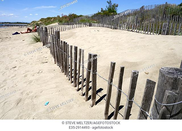 A fence holds back the dunes at the beach at Grau d'Agde, Herault, France