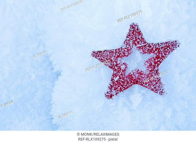 Red star Christmas decoration lying in snow, close-up