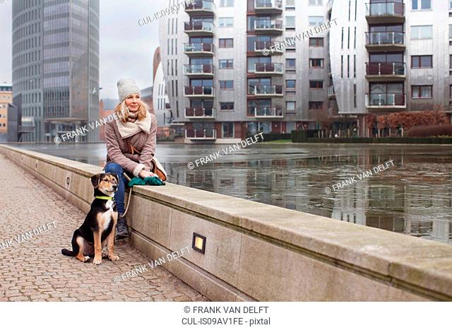 Mid adult woman and her dog sitting on riverside wall