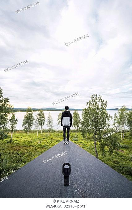Finland, Lapland, man standing on roof of a house at a lake