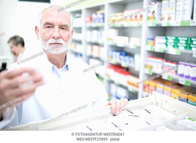 Pharmacist taking medicine from cabinet in pharmacy
