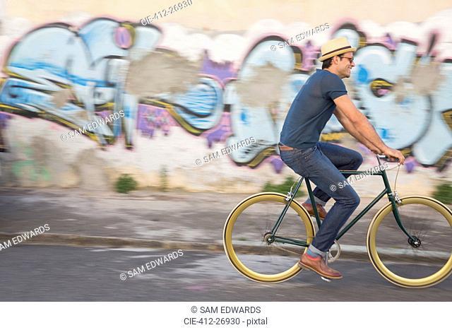 Hipster man riding bicycle on road along urban graffiti wall