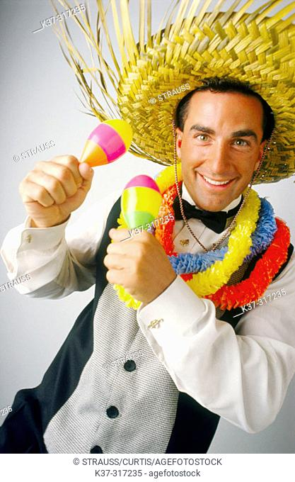 Caribbean style entertainer wearing palm frond hat and leis around his neck