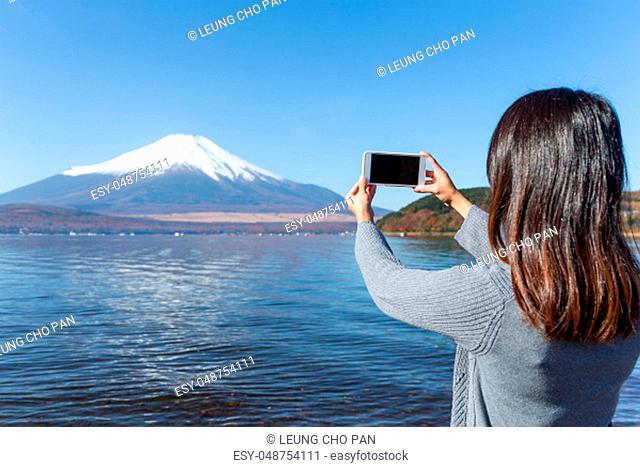 Woman take photo by mobile phone of Mount Fuji