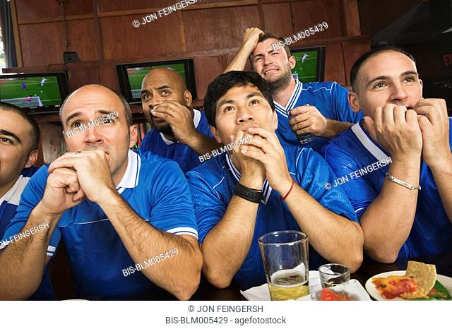 Worried teammates watching television in sports bar